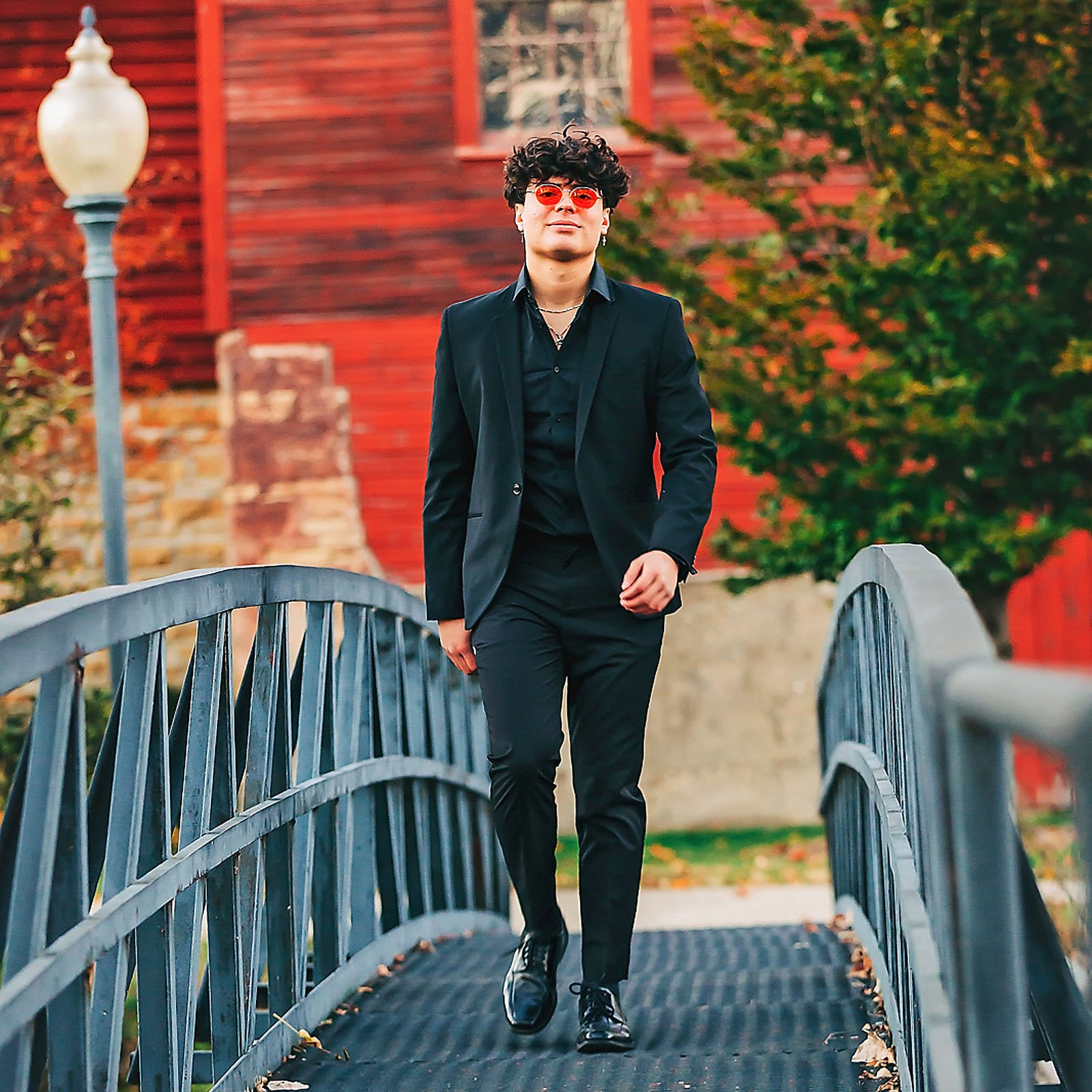 senior portraits; high school senior boy walking across a bridge