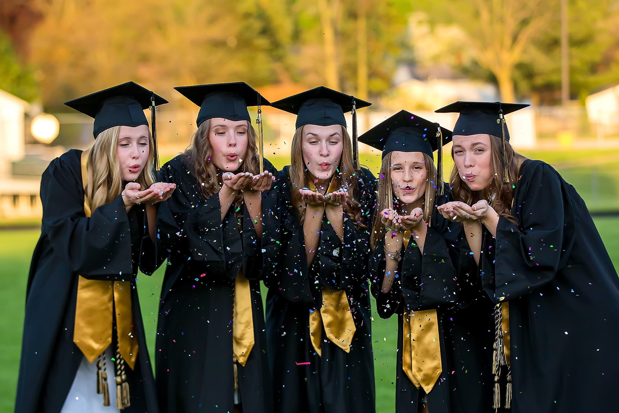 senior portraits; girls in graduation gowns blowing glitter